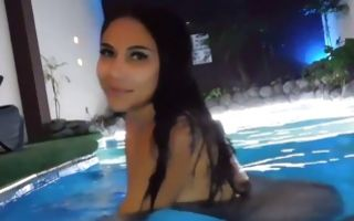Nude brunette in the pool exposing her boobs and her body