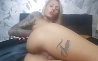 Hot bitch with a tattoo fingering her shaved vagina on the bed